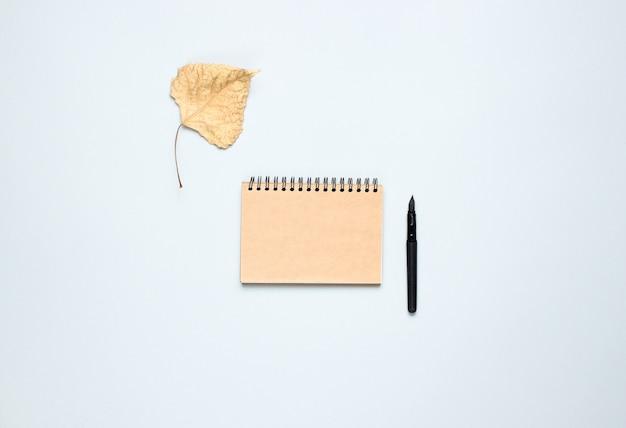 Notatnik z długopisem, opadłych liści jesienią na szarym stole. jesienna inspiracja, pisanie. widok z góry, minimalizm. leżał płasko