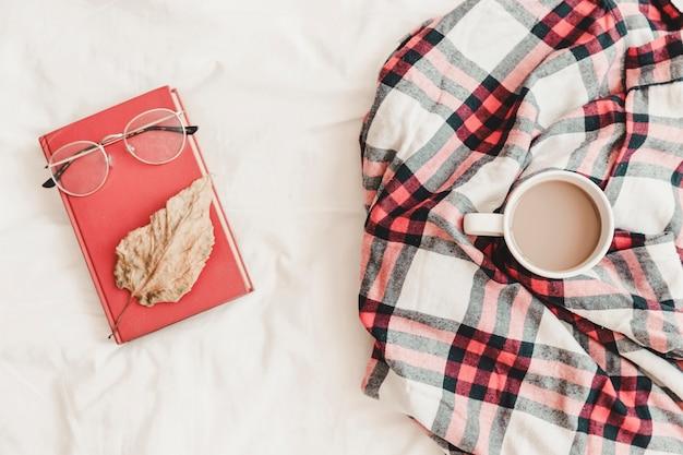 Notatnik z eyeglasses i liść na nim blisko ciepłego napoju w szkockiej kracie
