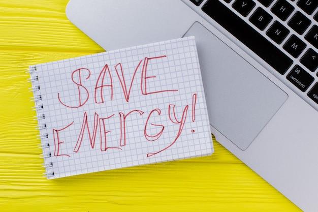 Notatnik z hasłem oszczędzania energii i klawiaturą laptopa. widok z góry na płasko. żółte drewniane tło.