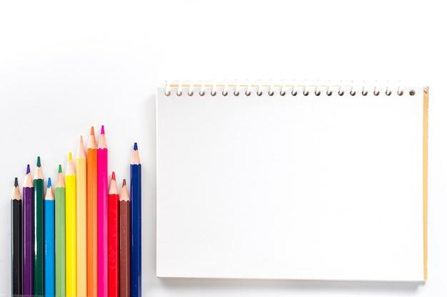 Notatnik z kolorowym ołówkiem na białym widoku stołu z góry