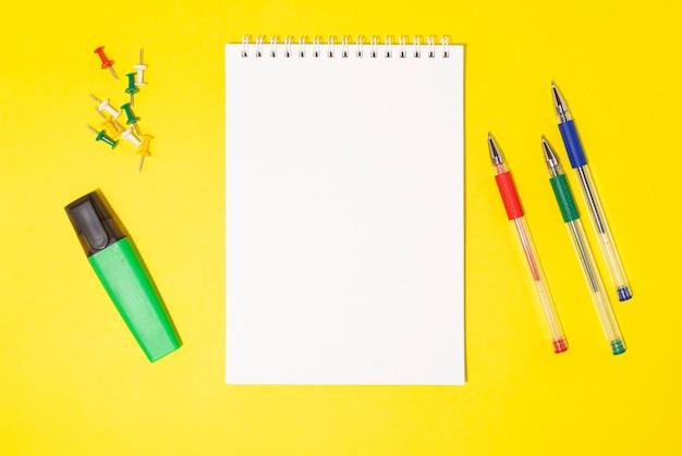Notatnik z kolorowymi długopisami na żółtym tle notatnik z markerem na żółtym tle
