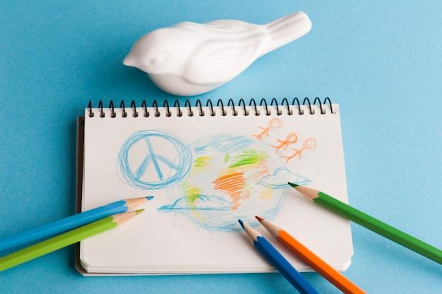Notatnik z kolorowymi kredkami i rysunkiem dziecka