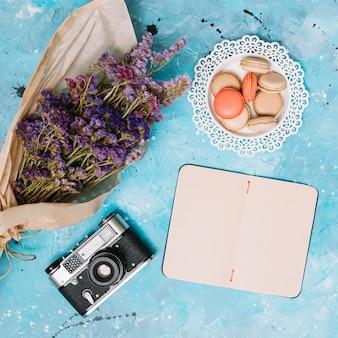 Notatnik z kwiatów bukietem, ciastkami i kamerą na stole