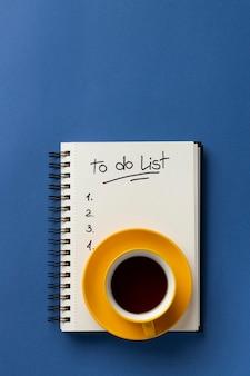 Notatnik z listą rzeczy do zrobienia na biurku z filiżanką kawy obok