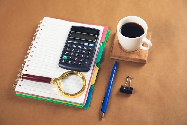 Notatnik z lupą i kalkulatorem z kawą na stole