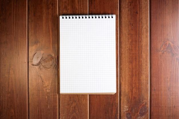 Notatnik z luźnymi kartkami w kratkę na ciemnym drewnianym blacie z miejscem na tekst