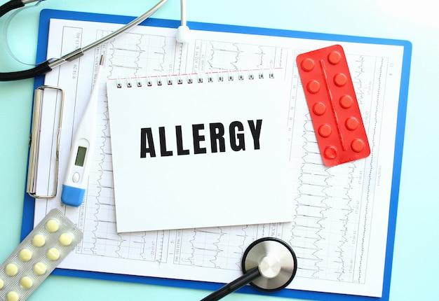 Notatnik z napisem alergia leży na niebieskim schowku medycznym ze stetoskopem i tabletkami na niebieskim tle. pojęcie medyczne.