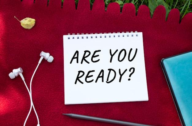 Notatnik z napisem are you ready. słuchawki są w pobliżu. czerwona krata i zielona trawa w tle.