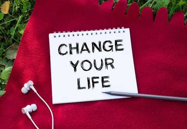 Notatnik z napisem change your life. słuchawki są w pobliżu. czerwona krata i zielona trawa w tle. koncepcja projektu.
