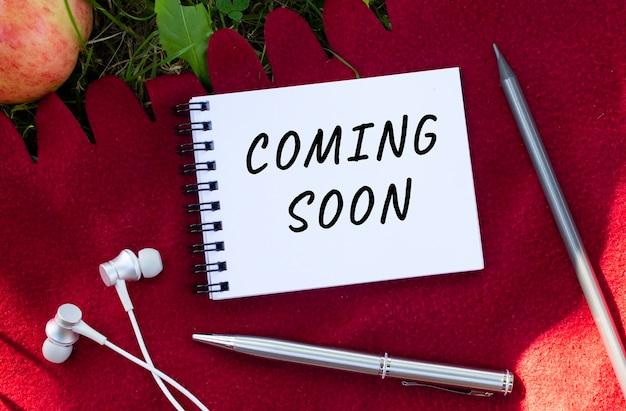 Notatnik z napisem coming soon. w pobliżu słuchawki i jabłko. czerwona krata i zielona trawa.