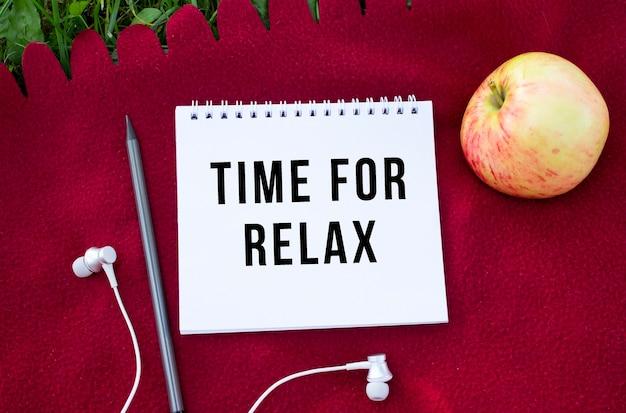 Notatnik z napisem czas na relaks. w pobliżu słuchawki i jabłko. czerwona krata i zielona trawa.