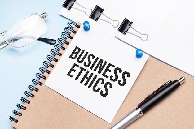 Notatnik z napisem etyka biznesu na biurku z okularami, notatnikiem i papierem ze spinaczami