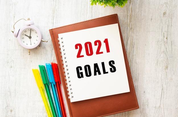 Notatnik z napisem goals 2021 na drewnianym stole. brązowy pamiętnik i długopisy