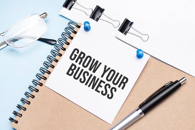 Notatnik z napisem grow your business na biurku z okularami, notatnikiem i papierem ze spinaczami.