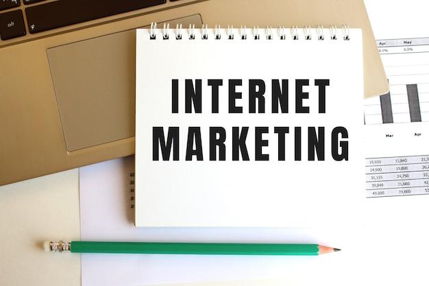 Notatnik z napisem internet marketing znajduje się na klawiaturze laptopa. pomysł na biznes.