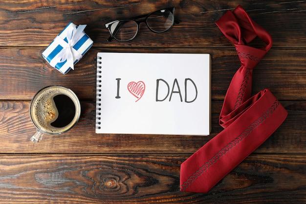 Notatnik z napisem kocham tatę, filiżankę kawy, szklanki, pudełko i krawat na drewniane tła