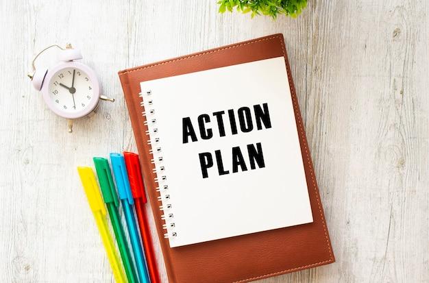 Notatnik z napisem plan działania na drewnianym stole. brązowy pamiętnik i długopisy. pomysł na biznes.
