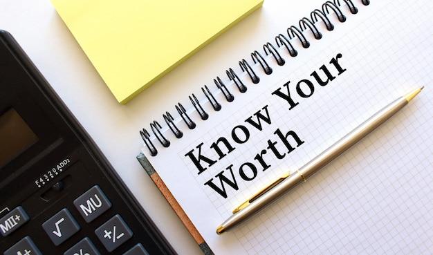 Notatnik z napisem poznaj swój warto obok niego znajduje się kalkulator