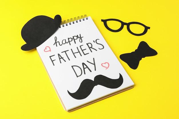 Notatnik z napisem szczęśliwy dzień ojców, dekoracyjne muszka, okulary, wąsy i kapelusz na kolor tła, miejsca na tekst