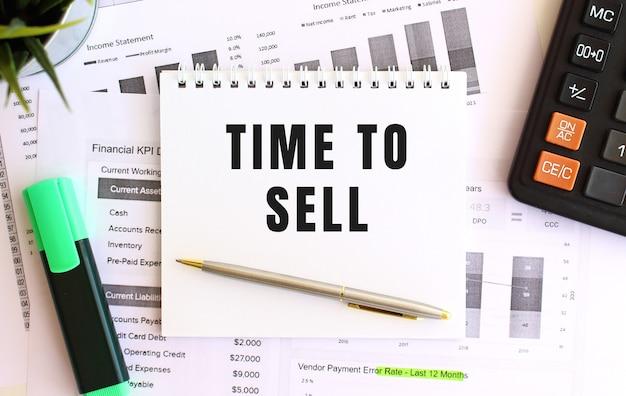 Notatnik z napisem time to sell na białym tle, w pobliżu markera, kalkulatora i materiałów biurowych. pomysł na biznes.