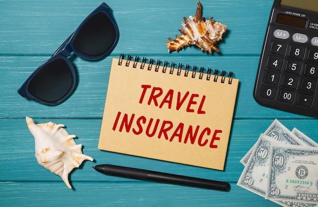Notatnik z napisem ubezpieczenie podróży, okulary, pieniądze, kalkulator i muszle