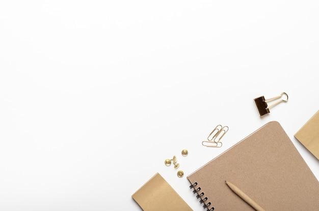 Notatnik z ołówkiem, guzikami, naklejkami, papeterią złotą na białym tle.