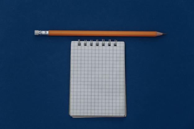 Notatnik z ołówkiem na klasycznym niebieskim tle. nowoczesne gadżety. kolor 2020. widok z góry.