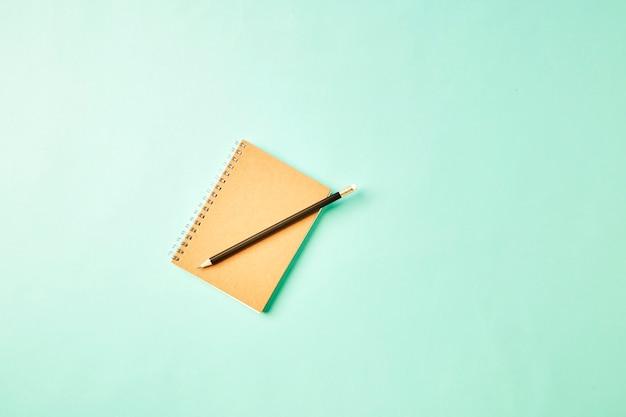 Notatnik z ołówkiem na pastelowym biurku