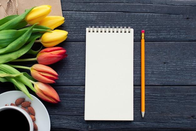 Notatnik z ołówkiem obok tulipanów.