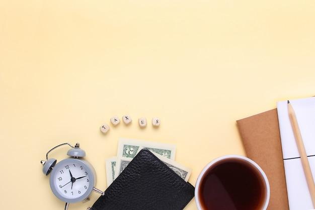 Notatnik z ołówkiem, portfelem, budzikiem, filiżanką kawy na beżowym tle z podatkami słownymi drewnianych liter.
