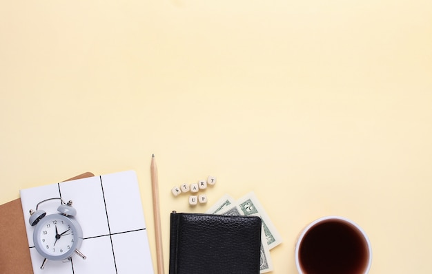Notatnik z ołówkiem, portfelem, budzikiem, filiżanką kawy na beżowym tle ze słowem uruchom drewniane litery.