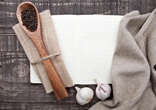 Notatnik z pieprzem na łyżce i kuchennym ręcznikiem na drewnianej desce