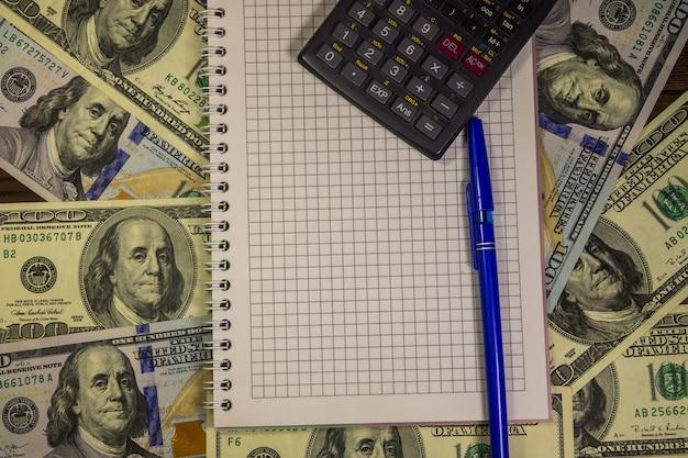 Notatnik z piórem i kalkulatorem na tle banknotów sto dolar amerykański. koncepcja finansowa
