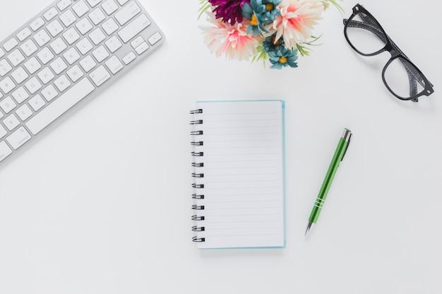 Notatnik z piórem i szkła blisko klawiatury i kwiatu na drewnianym stole