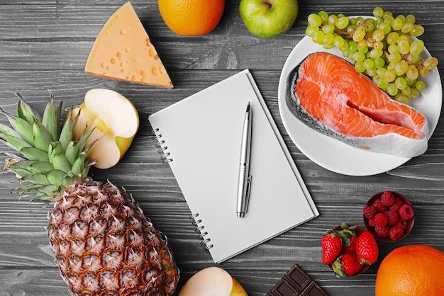 Notatnik z piórem i zdrową żywnością na niebieskim drewnianym stole