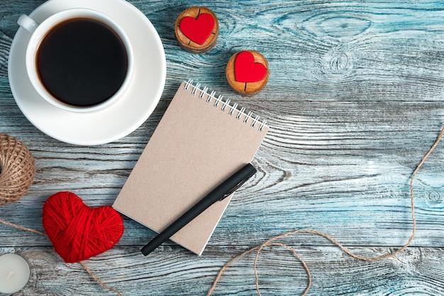 Notatnik z piórem, kawą i czerwonymi sercami na tle drewnianych.