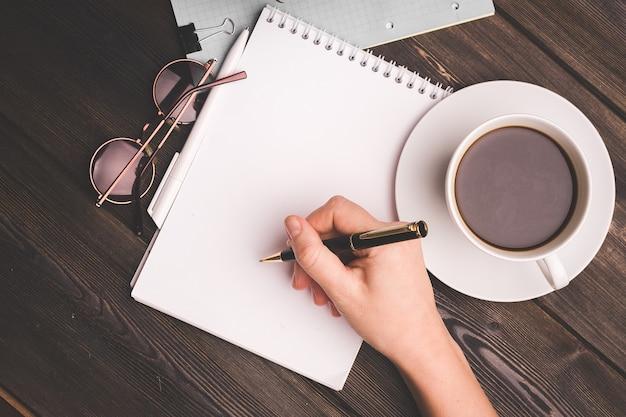 Notatnik z piórem na drewnianym stole filiżanka kawy biuro biznes finanse