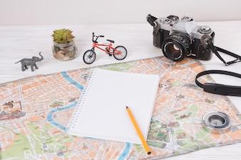 Notatnik z piórem na mapie w pobliżu zabawki zwierząt, kamery i rowerów