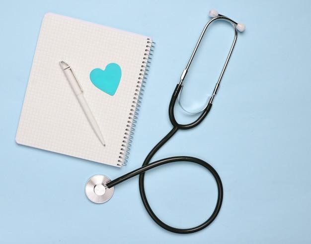 Notatnik z piórem, ozdobne serce, stetoskop na niebieskim pastelowym tle