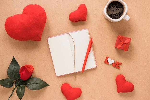 Notatnik z piórem w pobliżu ornament serca, kwiat i kubek napoju