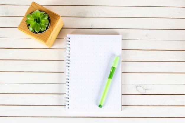 Notatnik z pióro reklamy rośliną w drewniany doniczkowym na białym tle