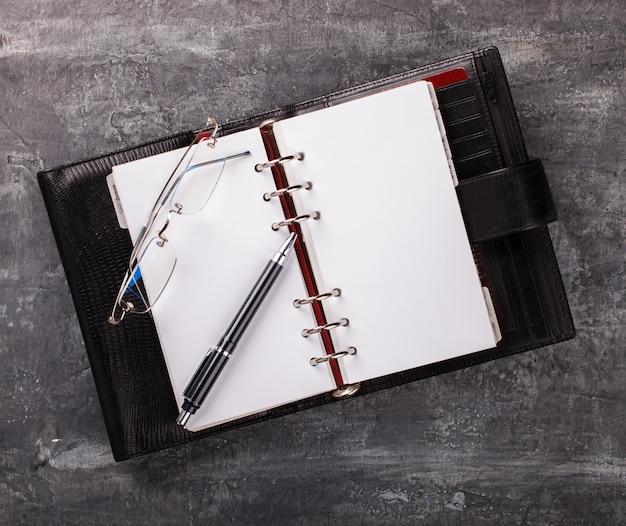 Notatnik z pióro szkłami biznesowy pojęcie