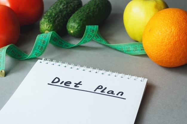 Notatnik z planem diety ze świeżymi warzywami i owocami na stole