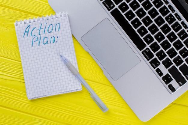 Notatnik z planem działania i laptopem. płaski widok z góry. żółte drewniane tło.