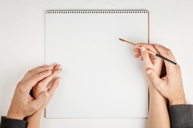 Notatnik z pustym arkuszem na białej ścianie z pędzlem w rękach, widok z góry. mieszkanie leżało z miejscem na kopię. koncepcja biura
