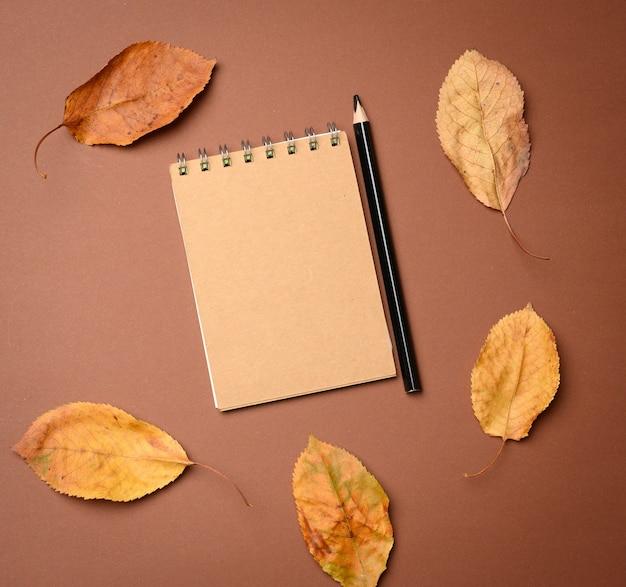 Notatnik z pustymi brązowymi kartkami na brązowym tle, widok z góry