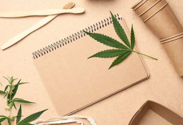 Notatnik z pustymi prześcieradłami i liściem marihuany