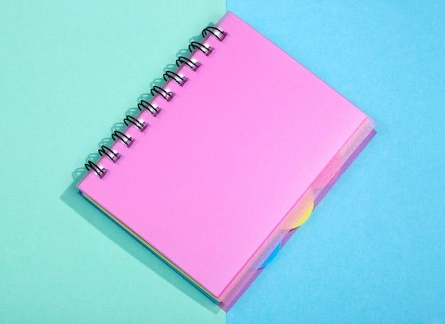 Notatnik z różową okładką na kolorowym tle