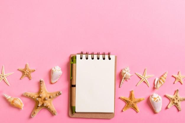 Notatnik z sseashells na różowym tło odgórnego widoku mieszkaniu nieatutowym. planowanie wakacji, turystyki i koncepcji wakacji