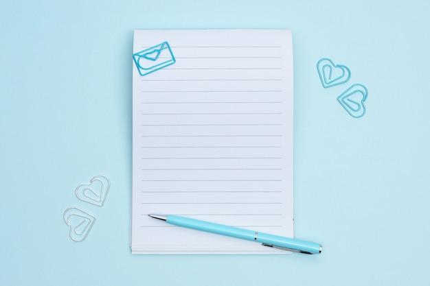 Notatnik z stacjonarnymi rzeczami na błękitnym tle. spinacze w kształcie serca wokół notebooka.